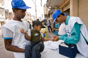Interact member, Rajkumar Shah, holds a boy up to the immunization table where he recieves an oral polio vaccine and get's his pinky marked, indicating immunization, during subnational immunization activiites in Birgunj, Nepal. Border towns in Nepal, with little regulations, like Birgunj, are high risk for the spread of the polio virus. Subnational immunization days take place more often than larger, annual events and target locations based on research by Rotary's polio eradication partners, the World Health Organization, UNICEF and the Center for Disease Control.